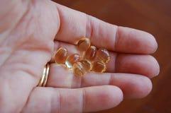 Gruppe klare Vitamingelkapseln oder Pillen in der Hand der Frau stockbild