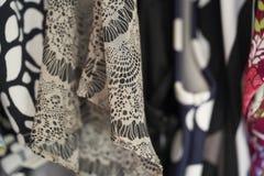 Gruppe Kleidung in einer Garderobe stockfotos