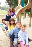Gruppe Kleinkinder, die auf Dia im Spielplatz sitzen Lizenzfreie Stockfotos