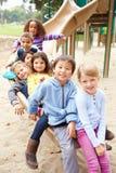 Gruppe Kleinkinder, die auf Dia im Spielplatz sitzen Stockbilder