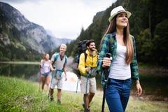 Gruppe lächelnde Freunde, die draußen mit Rucksäcken wandern Reise, Tourismus, Wanderung und Leutekonzept stockfotografie