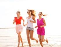 Gruppe lächelnde Frauen, die auf Strand laufen Stockfoto