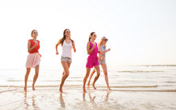 Gruppe lächelnde Frauen, die auf Strand laufen Stockfotos