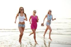 Gruppe lächelnde Frauen, die auf Strand laufen Stockbilder