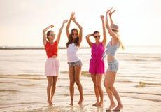 Gruppe lächelnde Frauen, die auf Strand tanzen stockfoto