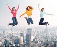 Gruppe lächelnde Frauen, die in einer Luft springen Lizenzfreies Stockfoto