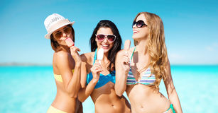 Gruppe lächelnde Frauen, die Eiscreme auf Strand essen Stockbild