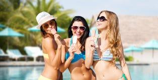 Gruppe lächelnde Frauen, die Eiscreme auf Strand essen Stockfotos