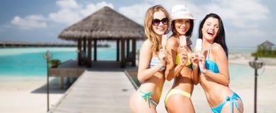 Gruppe lächelnde Frauen, die Eiscreme auf Strand essen Lizenzfreies Stockbild
