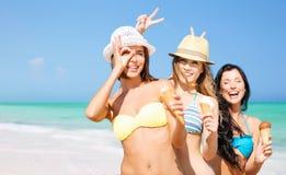 Gruppe lächelnde Frauen, die Eiscreme auf Strand essen Lizenzfreie Stockfotografie