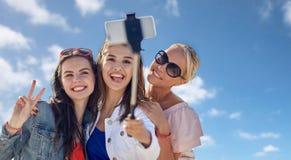Gruppe lächelnde Frauen, die selfie über blauem Himmel nehmen Lizenzfreie Stockfotografie