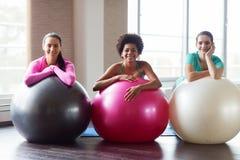 Gruppe lächelnde Frauen mit Übungsbällen in der Turnhalle stockbild