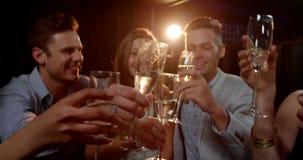 Gruppe lächelnde Freunde, die auf Sofa sitzen und Gläser Champagner rösten stock video