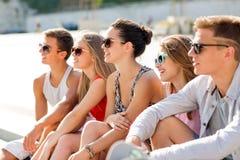Gruppe lächelnde Freunde, die auf Stadtplatz sitzen Lizenzfreies Stockfoto