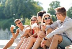 Gruppe lächelnde Freunde, die auf Stadtplatz sitzen Lizenzfreie Stockfotografie