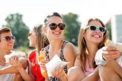 Gruppe lächelnde Freunde, die auf Stadtplatz sitzen Stockbilder