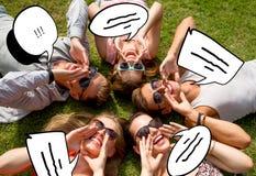 Gruppe lächelnde Freunde, die draußen auf Gras liegen Stockbilder