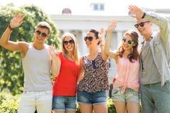 Gruppe lächelnde Freunde, die draußen Hände wellenartig bewegen Lizenzfreies Stockfoto