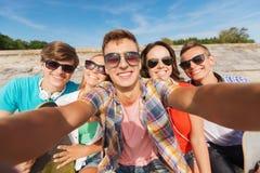 Gruppe lächelnde Freunde, die draußen selfie machen lizenzfreie stockfotos