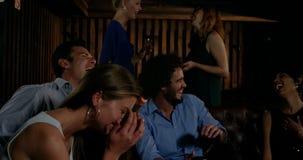 Gruppe lächelnde Freunde, die Spaß in der Stange haben stock footage