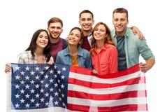 Gruppe lächelnde Freunde mit amerikanischer Flagge stockfotos