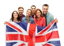 Gruppe lächelnde Freunde mit britischer Flagge lizenzfreie stockfotos