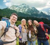 Gruppe lächelnde Freunde mit dem Rucksackwandern Stockfotos
