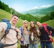 Gruppe lächelnde Freunde mit dem Rucksackwandern Stockbild