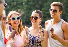 Gruppe lächelnde Freunde mit Eiscreme draußen Stockbilder