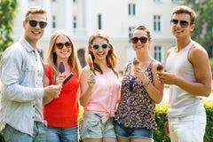 Gruppe lächelnde Freunde mit Eiscreme draußen Lizenzfreie Stockfotografie
