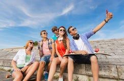 Gruppe lächelnde Freunde mit Smartphone draußen Lizenzfreie Stockfotografie