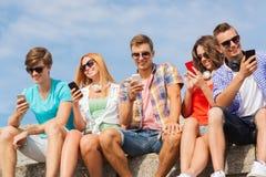 Gruppe lächelnde Freunde mit Smartphones draußen Lizenzfreie Stockfotografie