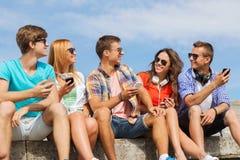 Gruppe lächelnde Freunde mit Smartphones draußen Stockfotografie