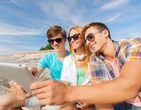 Gruppe lächelnde Freunde mit Tabletten-PC draußen Lizenzfreies Stockfoto