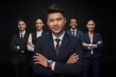 Gruppe lächelnde Geschäftsleute, die mit den Armen gekreuzt stehen und Kamera betrachten lizenzfreie stockfotografie