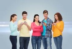 Gruppe lächelnde Jugendliche mit Smartphones Stockfoto