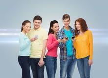 Gruppe lächelnde Jugendliche mit Smartphones Stockbilder