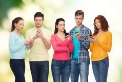 Gruppe lächelnde Jugendliche mit Smartphones Lizenzfreies Stockbild