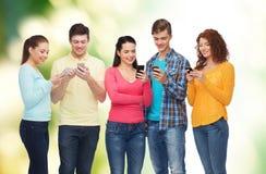 Gruppe lächelnde Jugendliche mit Smartphones Lizenzfreie Stockfotografie