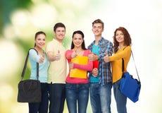 Gruppe lächelnde Jugendlichen, die sich Daumen zeigen Lizenzfreie Stockfotos