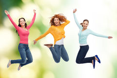 Gruppe lächelnde junge Frauen, die in einer Luft springen Stockfotos