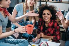 Gruppe lächelnde junge Frauen, die Kaffee trinken und zusammen studieren Stockbilder