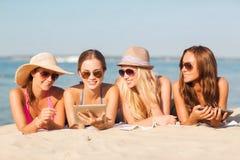 Gruppe lächelnde junge Frauen mit Tabletten auf Strand Stockbilder