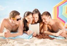Gruppe lächelnde Leute mit Tabletten-PC auf Strand Lizenzfreie Stockbilder