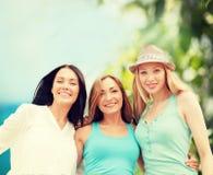 Gruppe lächelnde Mädchen, die auf dem Strand kühlen lizenzfreies stockfoto