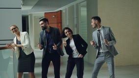 Gruppe lächelnde Mitarbeiter der jungen Leute in der formalen Kleidung tanzt in Lobby des modernen Bürogebäudes, das Spaß hat stock footage
