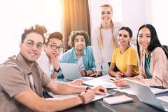 Gruppe lächelnde multikulturelle Teilhaber, die bei Tisch mit Laptops und Papieren während des Treffens an modernem sitzen lizenzfreie stockfotos
