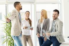 Gruppe lächelnde stehende und in Verbindung stehende Geschäftsleute stockfotografie
