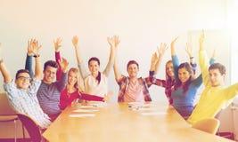 Gruppe lächelnde Studenten, die Hände im Büro anheben stockfoto
