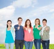 Gruppe lächelnde Studenten, die sich Daumen zeigen Lizenzfreie Stockbilder